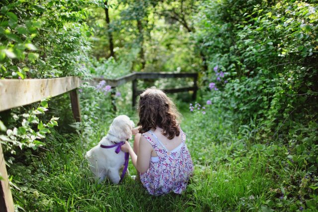 Girl and puppy sitting on green grass surrounded with plants during daytime